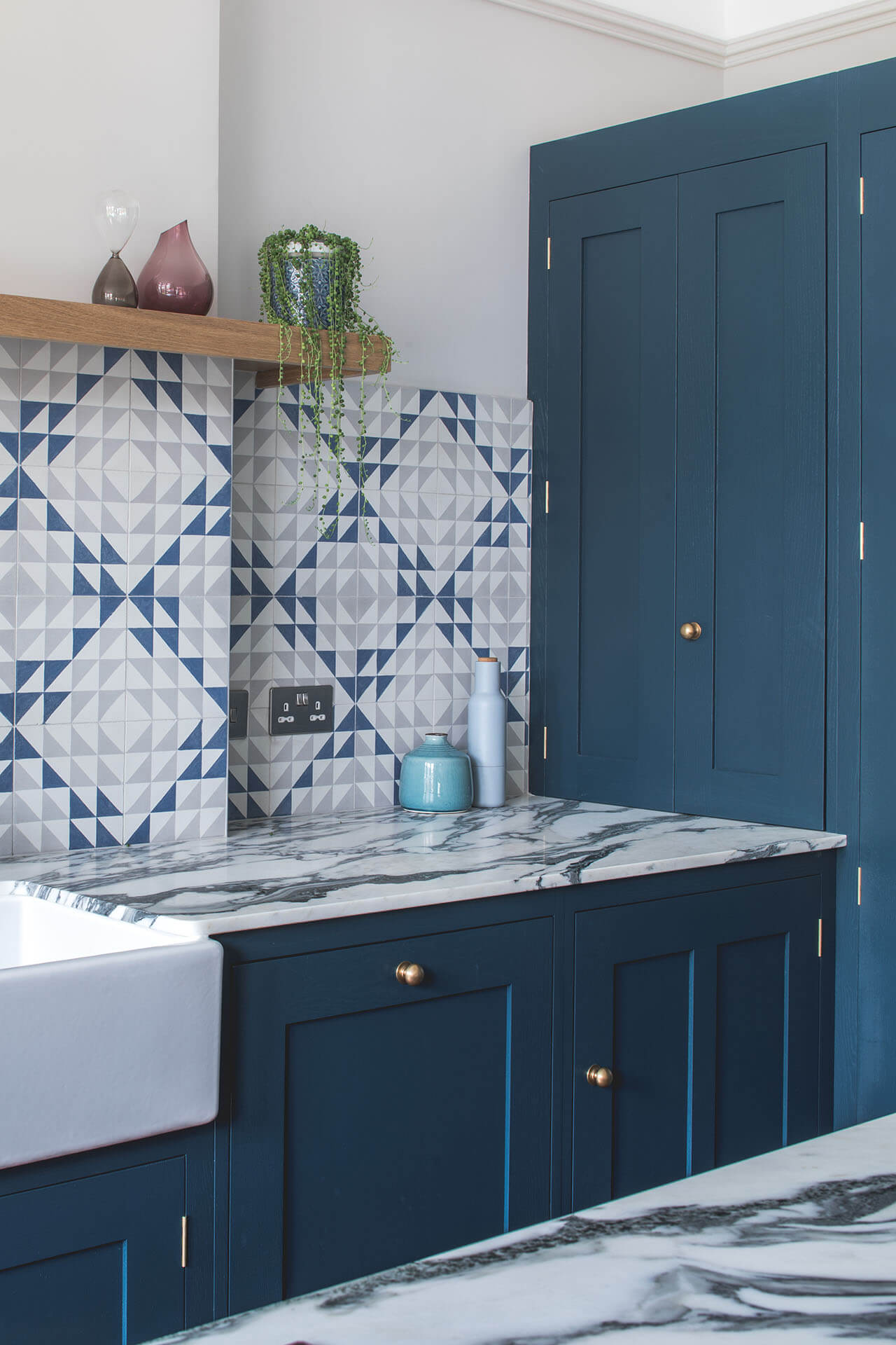 Dark blue geometric kitchen with tall cabinets and marble worktop
