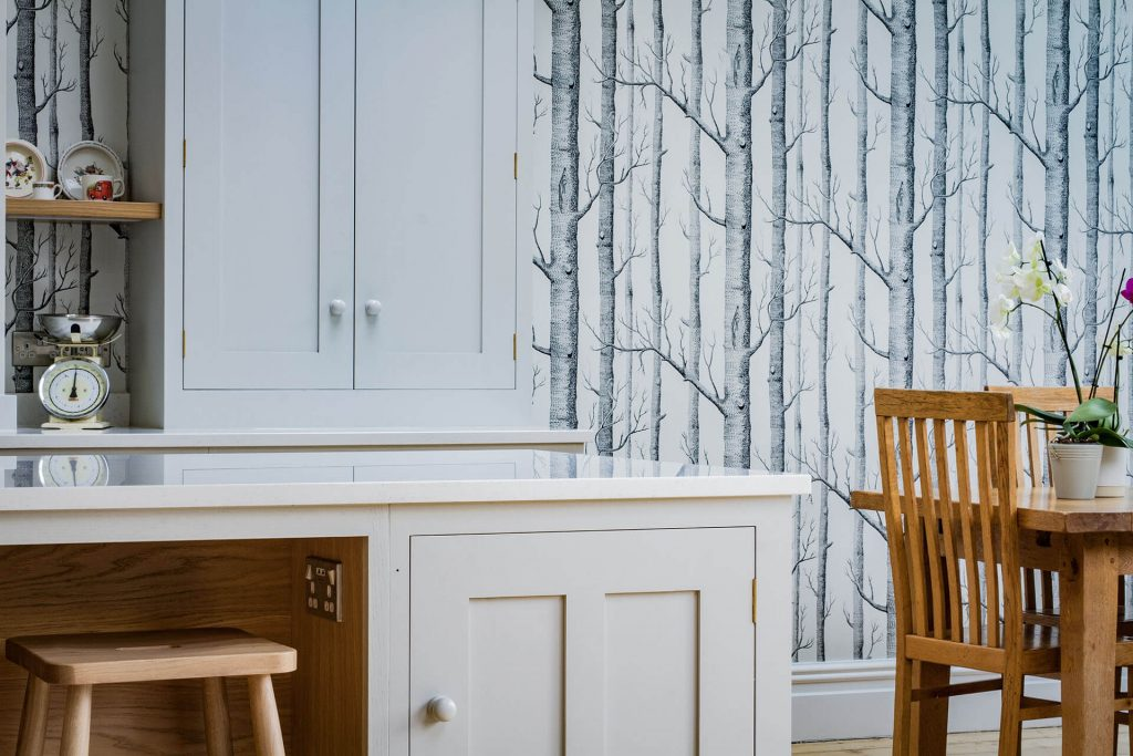 Scandinavian Woodland Kitchen with painted shaker cabinets and woodland wallpaper