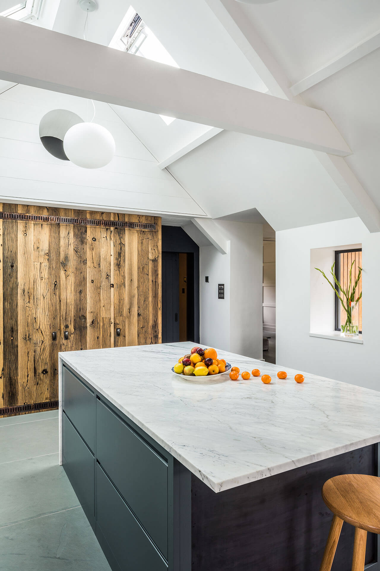 Steel, Marble, Reclaimed Wood Kitchen with a Calacatta Venato marble breakfast bar on the island