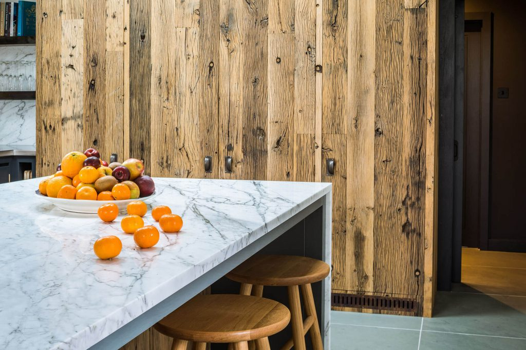 Steel, Marble, Reclaimed Wood Kitchen with breakfast bar and waterfall Calacatta Venato marble worktop on the island