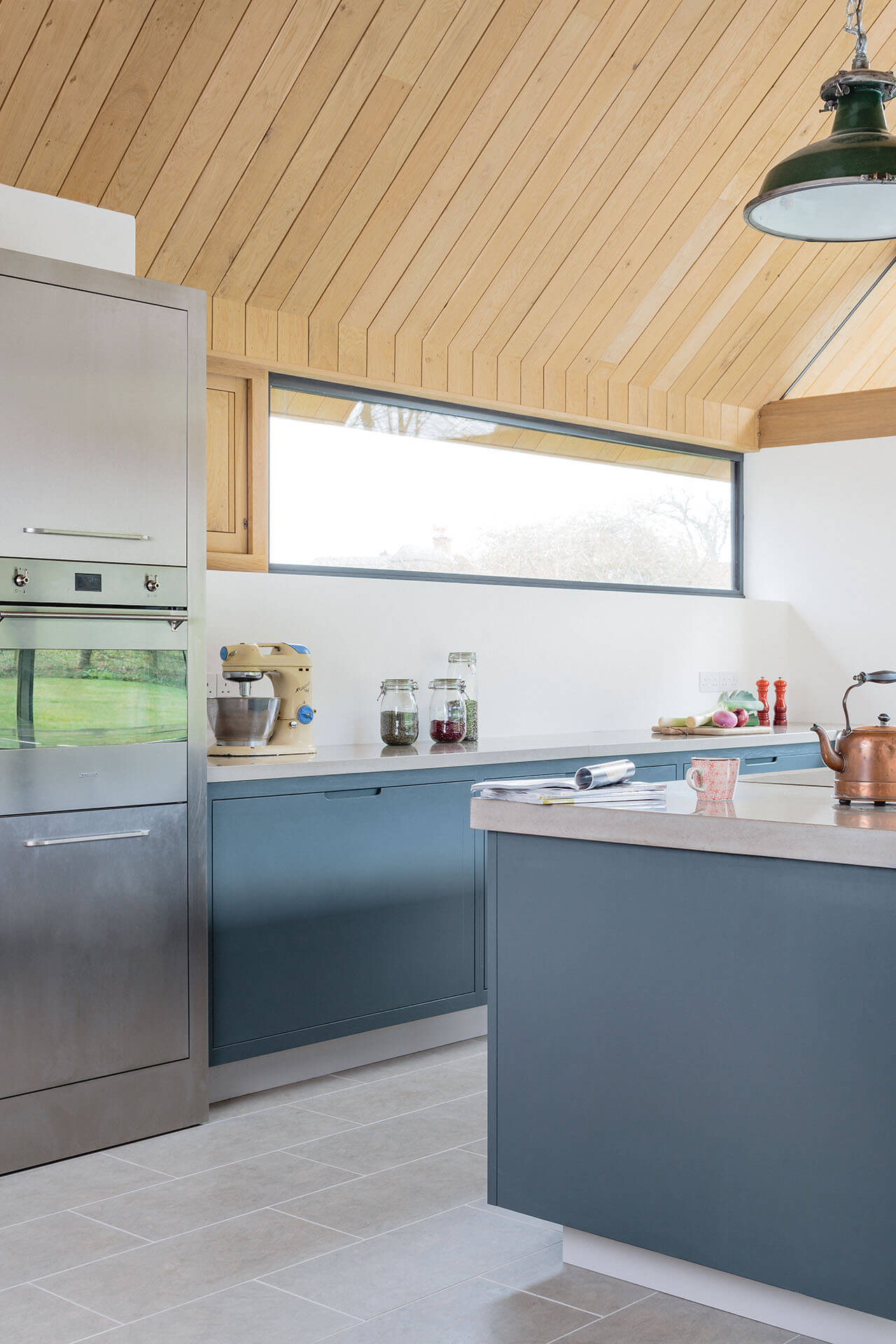 The vine house modern kitchen with conrete worktops and natural stone flooring