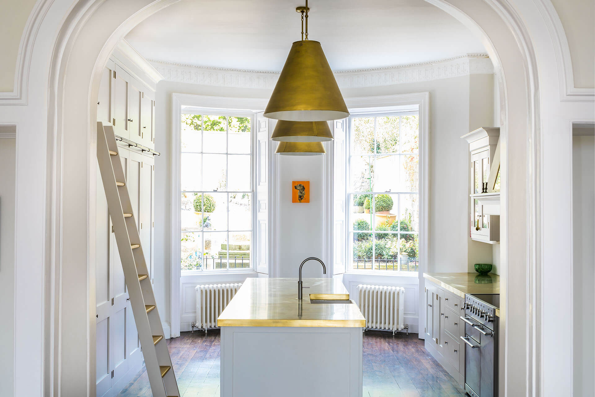 White Shaker Kitchen with large kitchen island, brass worktops and brass pendant lights