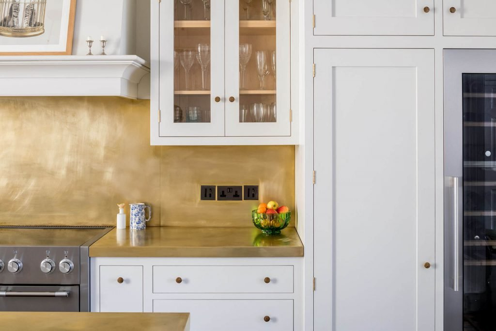 White Shaker Kitchen with tall cabinets and brass splashback