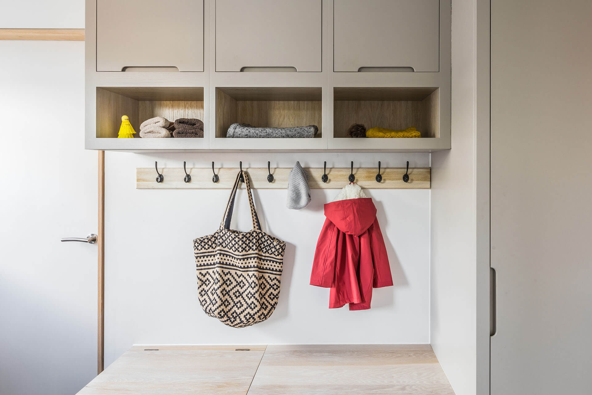 Contemporary grey industrial kitchen with boot room storage and coat hooks
