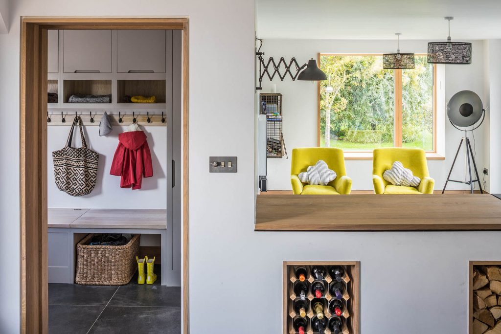 Contemporary grey industrial kitchen with boot room storage, bespoke wine cabinet and log store and Oak worktops