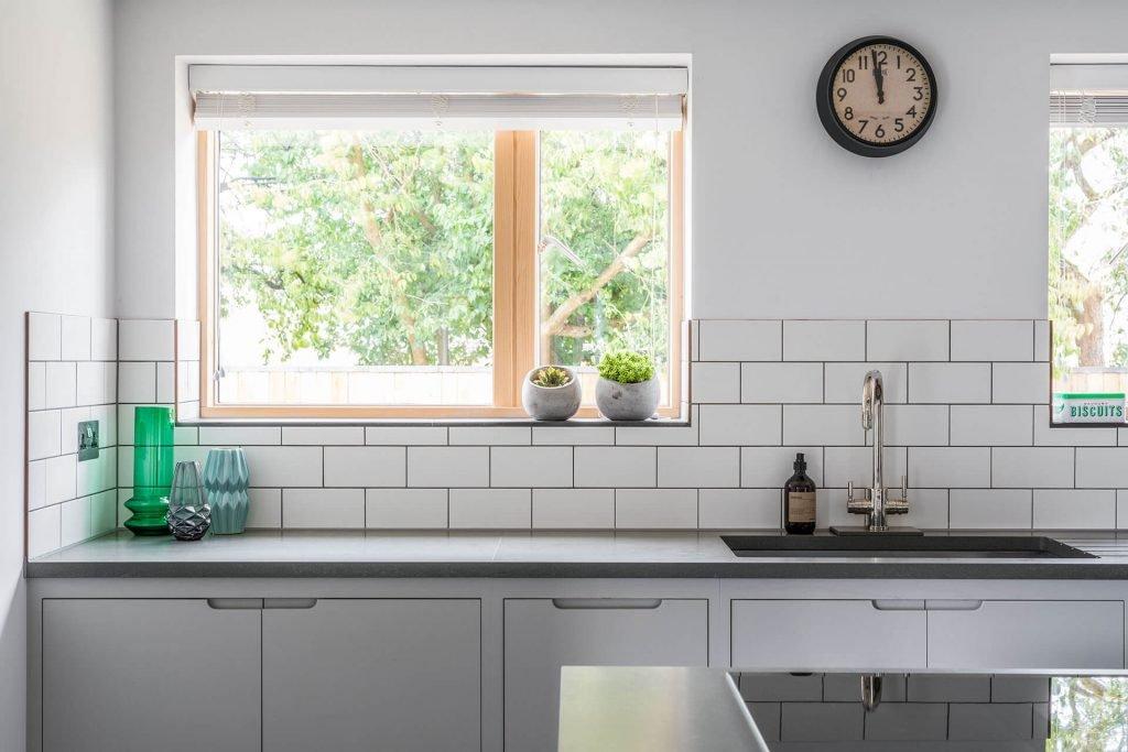 Contemporary grey industrial kitchen with white metro tile splashback