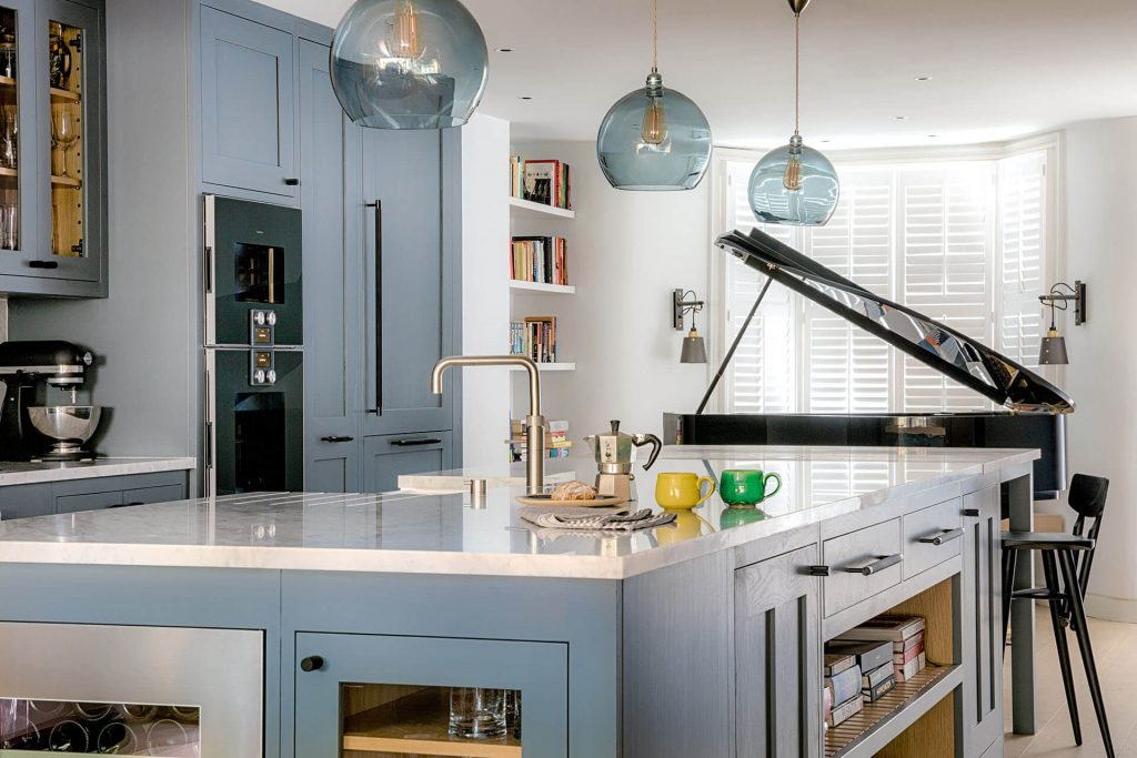 Grand Grey Shaker Kitchen with grey painted cabinets and island with carrara marble worktop with baby grand piano in the background
