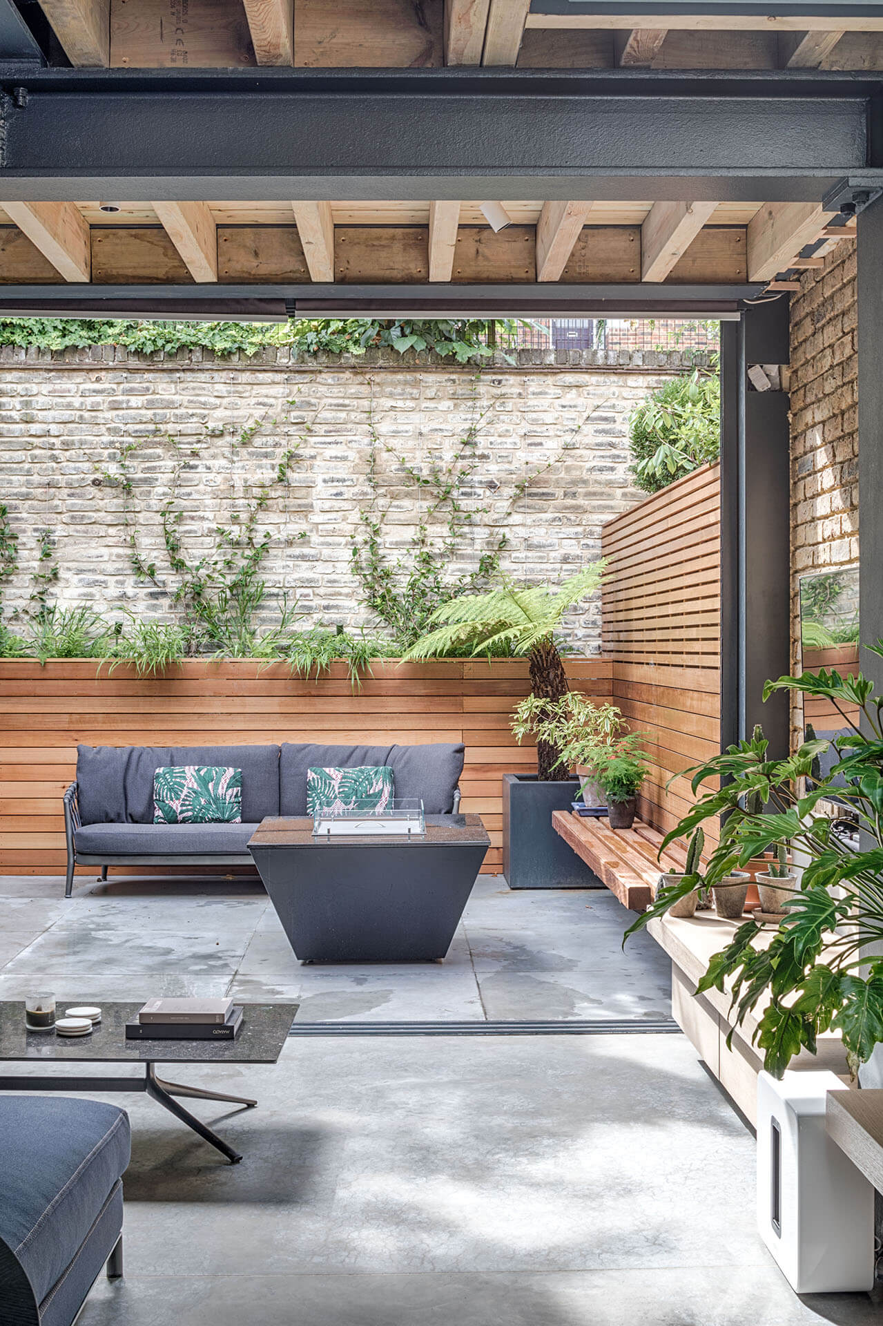 Grand Grey Shaker Kitchen with living area opening onto the garden with slatted wooden planters and outdoor seating