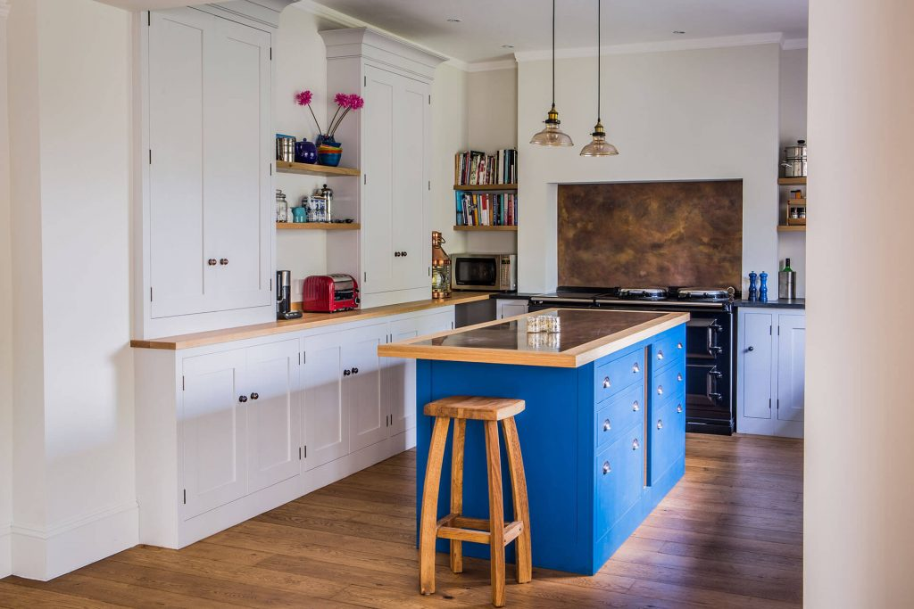Antiqued brass contemporary kitchen with blue centre island and Ammonite shaker cabinets