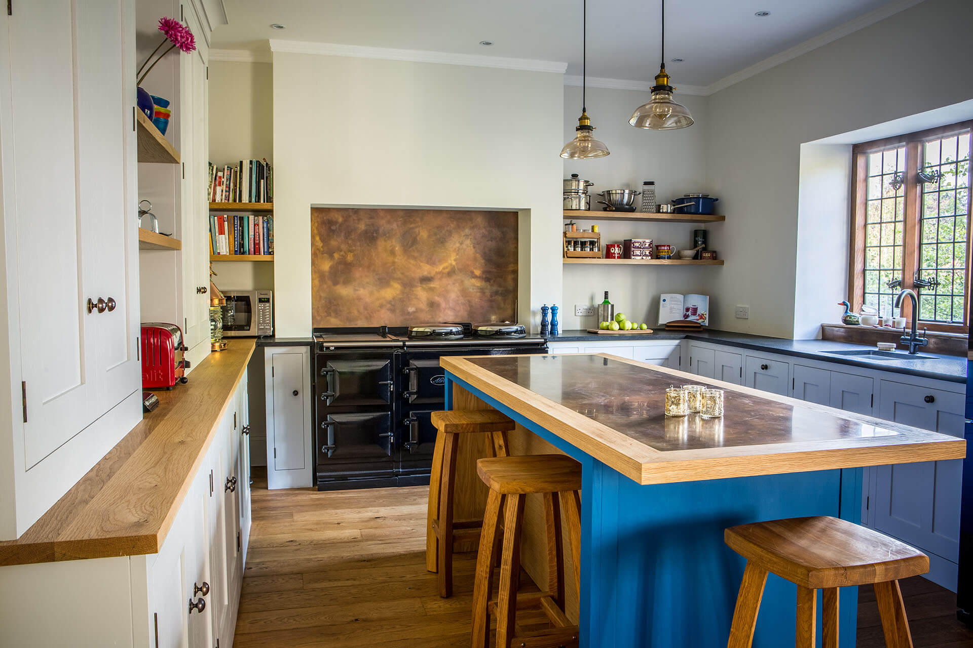 Antiqued brass contemporary kitchen with kitchen centre island and Oak breakfast bar