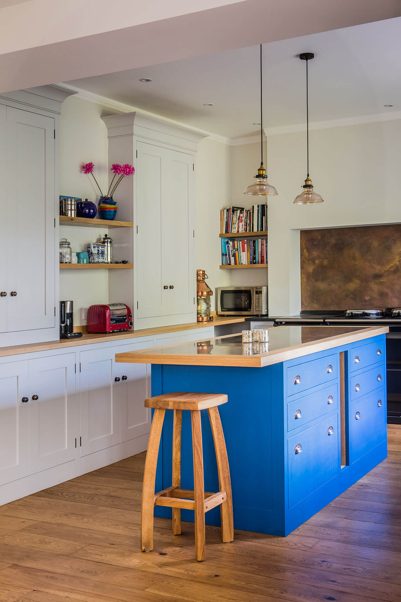 Antiqued brass contemporary kitchen with tall half larder cabinets and blue kitchen island