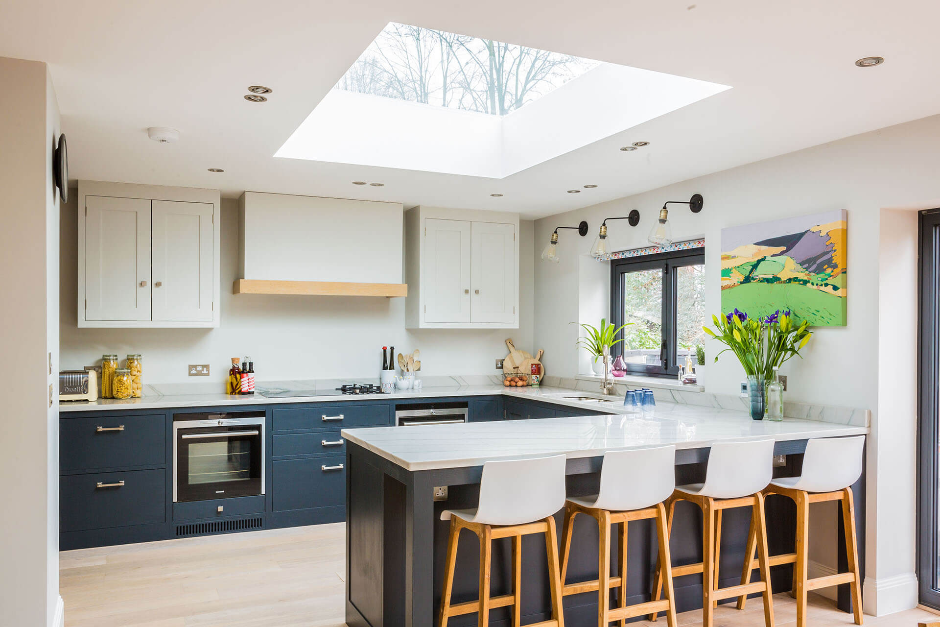 Light and airy london Shaker kitchen with large peninsular and white quartz worktop