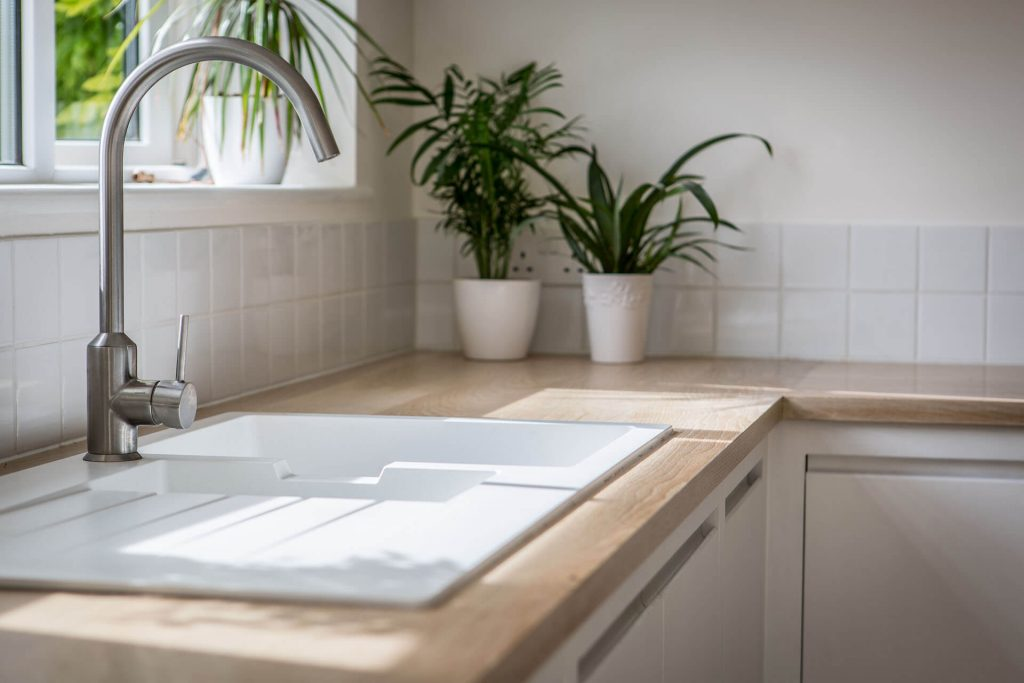 Minimalist contemporary white kitchen with Ikea Hallviken sink and Oak worktop