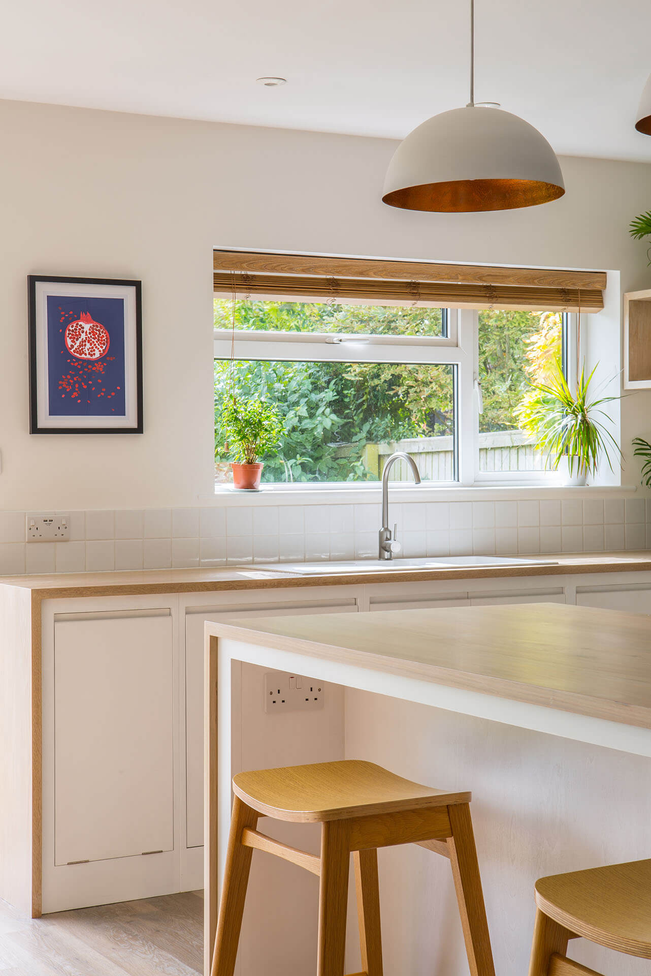 Minimalist contemporary white kitchen with breakfast bar and Oak worktop with waterfall ends