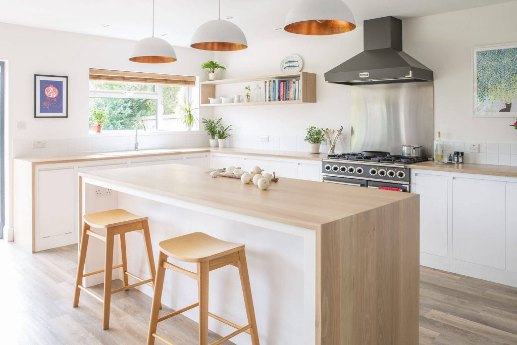 Minimalist contemporary white kitchen with large centre island, Falcon range cooker and Oak worktop