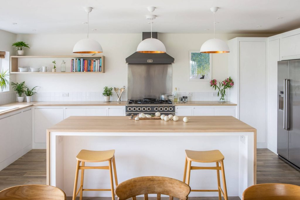 Minimalist contemporary white kitchen with large wrap around Oak worktop on centre island, breakfast bar seating and falcon range cooker
