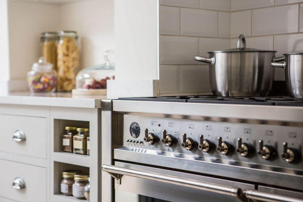 Open plan white Shaker kitchen with Smeg range cooker and quartz worktop
