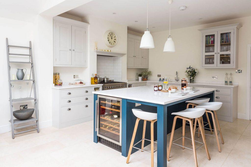 Open plan white Shaker kitchen with large kitchen centre island and white quartz worktop