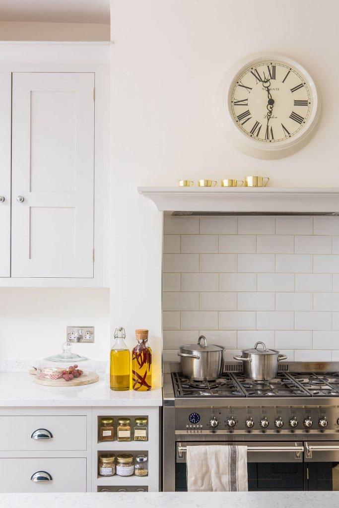 Open plan white Shaker kitchen with white metro tile splashback and white quartz worktop