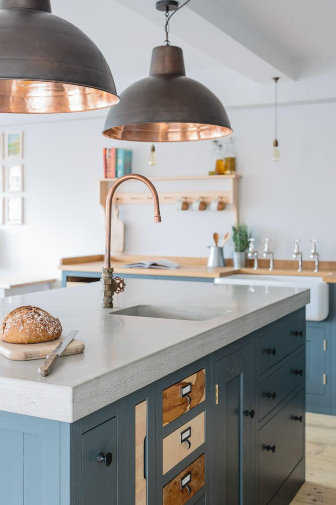 Sustainable Kitchens Showroom with large bespoke centre island and copper pendant lights