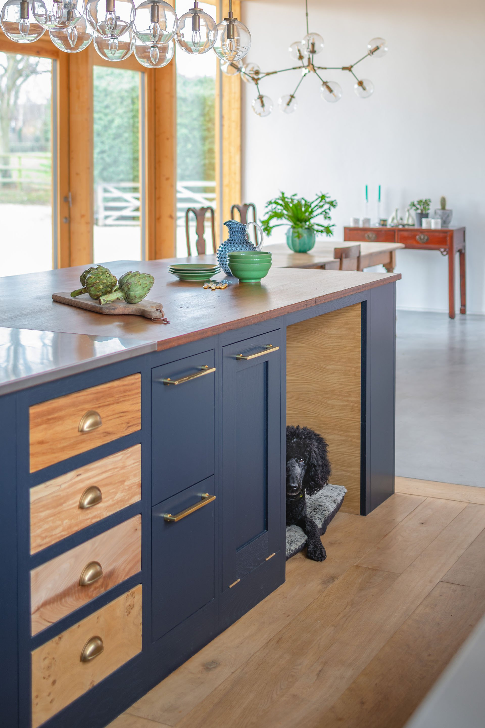 Eco Extension Shaker Kitchen with bespoke dog bed, art deco lighting and floor to ceiling windows looking out onto the garden