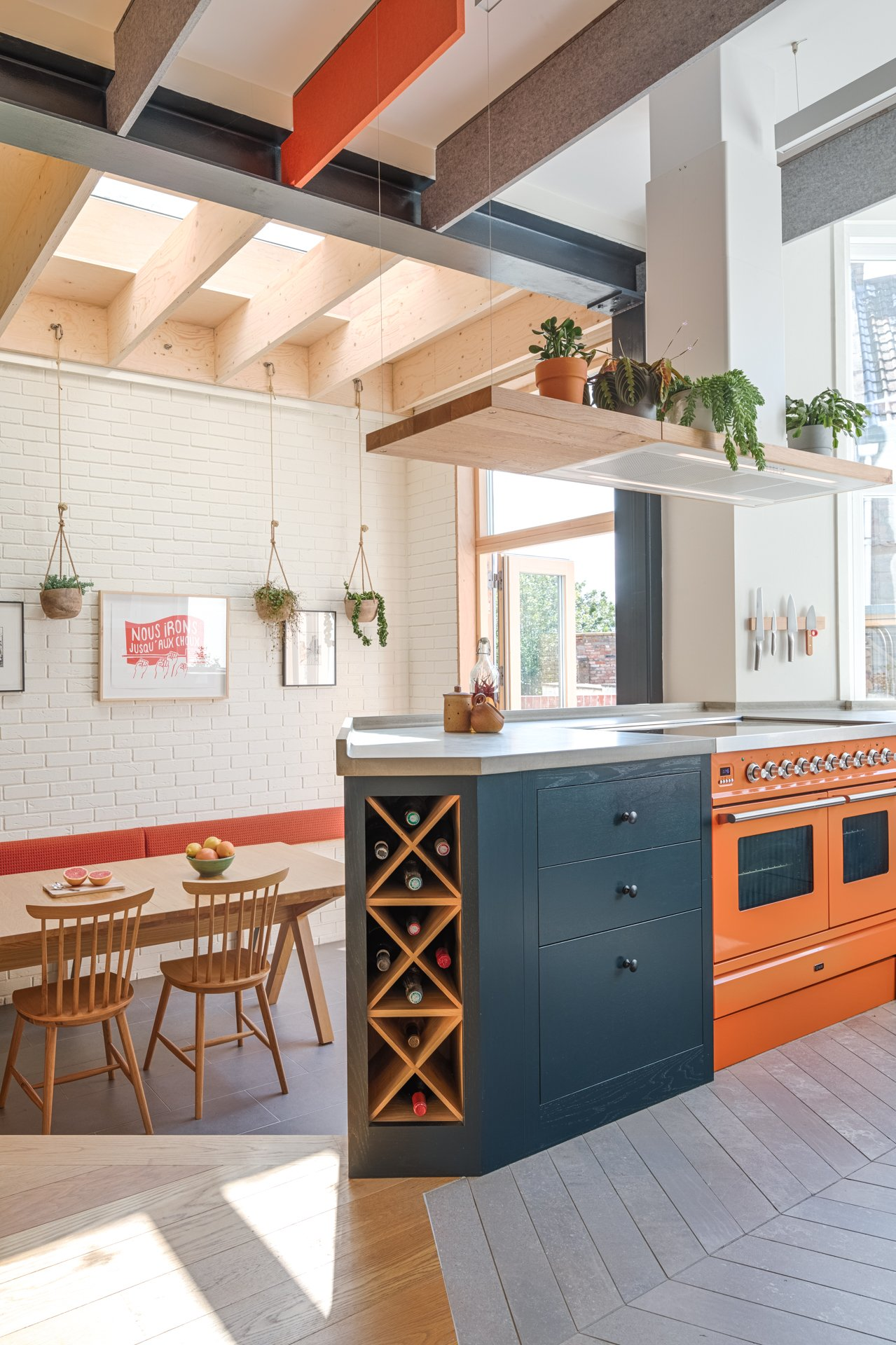 The loft kitchen Farrow and Ball Railings peninsular island with Ilve Roma 100 range in orange charlottes locks and Elica bio island extractor fan