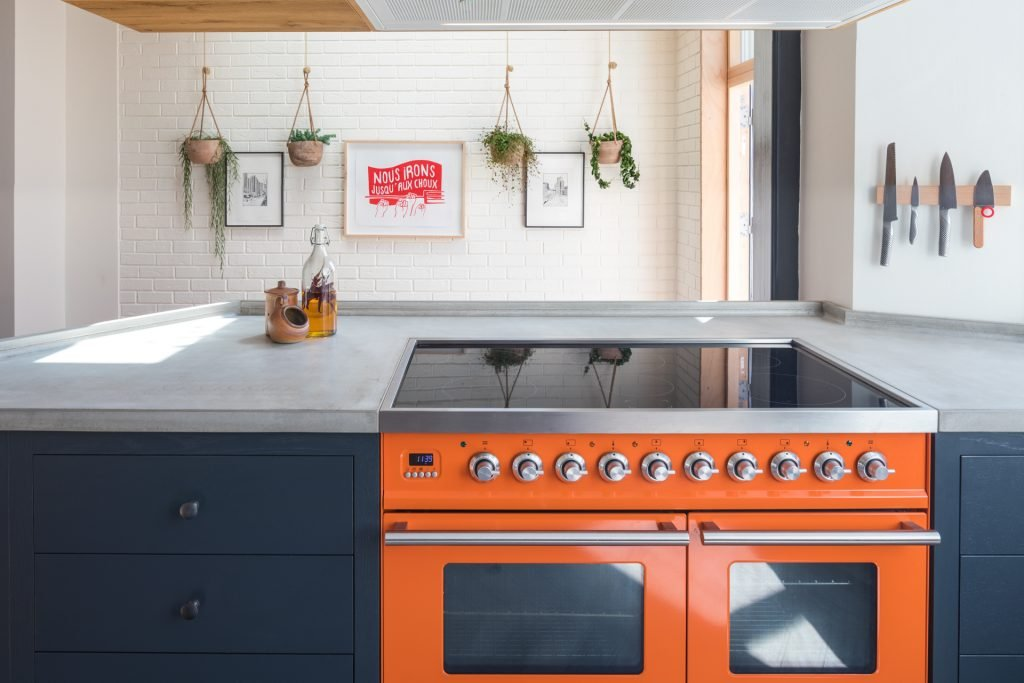 The loft kitchen Ilve Roma range charlottes locks with chefs knives plants and concrete worktop