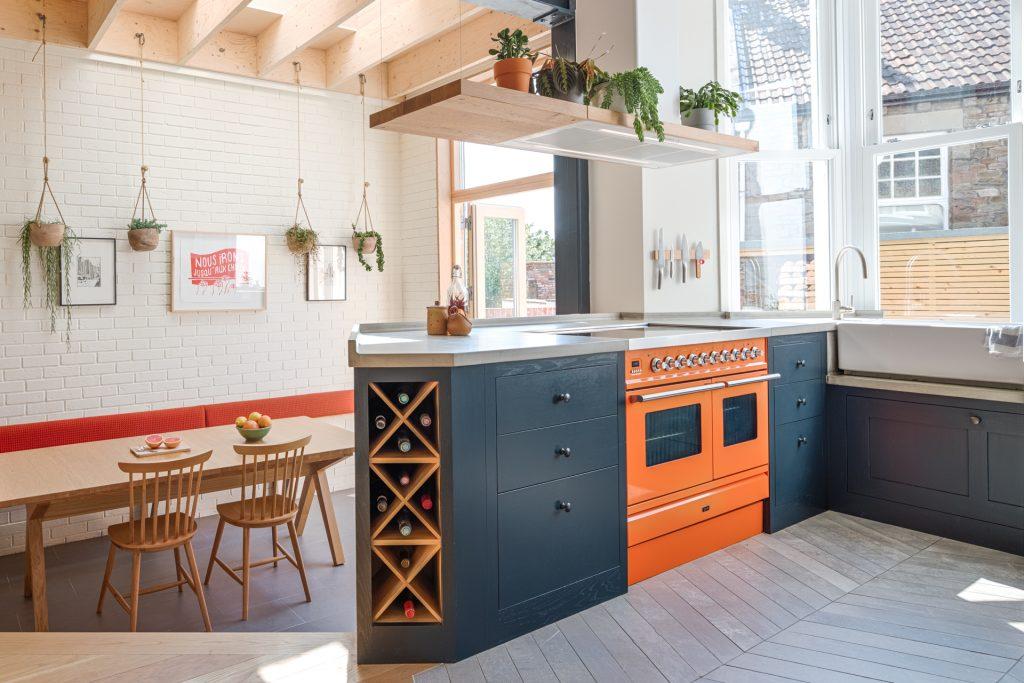 The loft kitchen peninsular island with Ilve Roma 100 range in orange charlottes locks and Elica bio island extractor fan