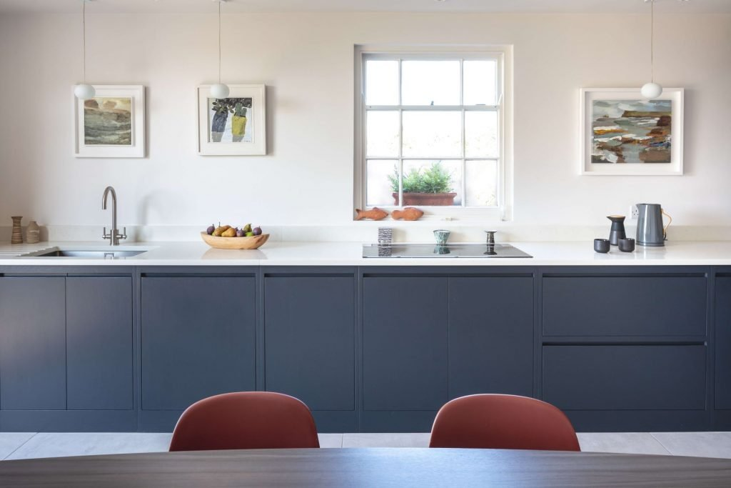 L shape contemporary kitchen with james burleigh table, normann chairs in farrow and ball railings