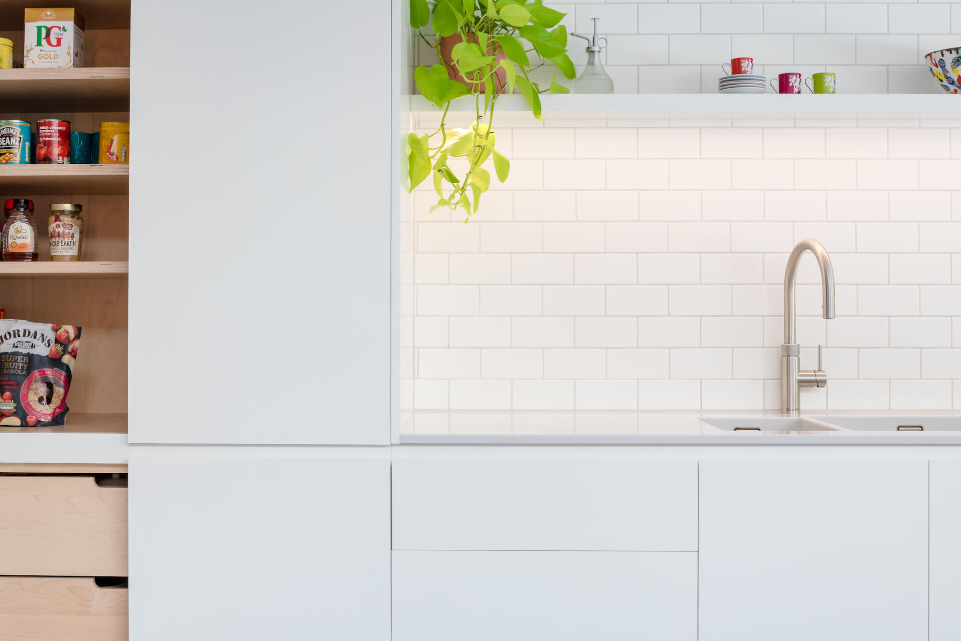 Contemporary White Kitchen with white corian worktop and quooker tap - Sustainable Kitchens